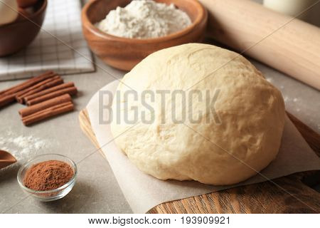 Raw dough with ingredients for cinnamon roll on kitchen table