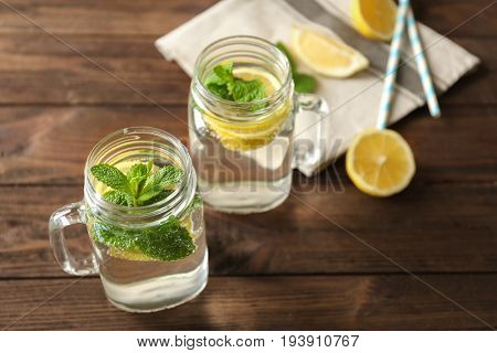 Refreshing lemon water in glass mason jars on wooden table