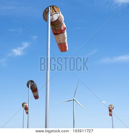 wind turbine and windbag as silhouette against blue sky with fluffy clouds