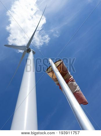 wind turbine and windbag as silhouette against blue sky and white cloud