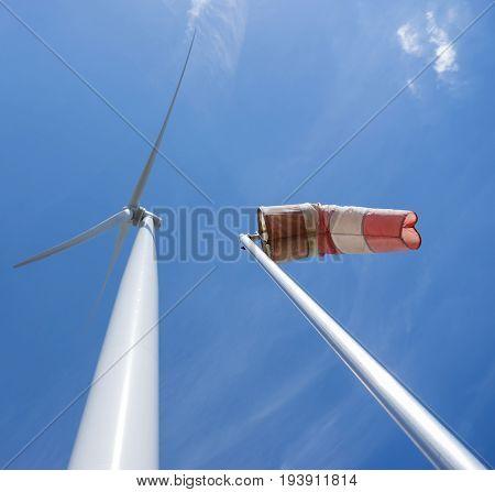 wind turbine and windbag as silhouette against blue sky