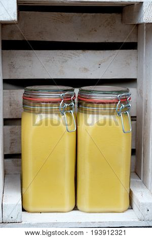 Ghee in Jar. Ghee oil. Two jars on a wooden background
