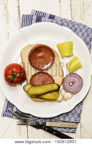 grilled scalded sausage a slice of bread with fresh tomato gherkin yellow paprika onion and garlic on a plate poster