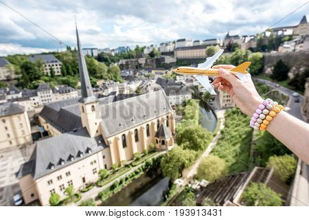 Holding a toy airplane on the old town background in Luxembourg city