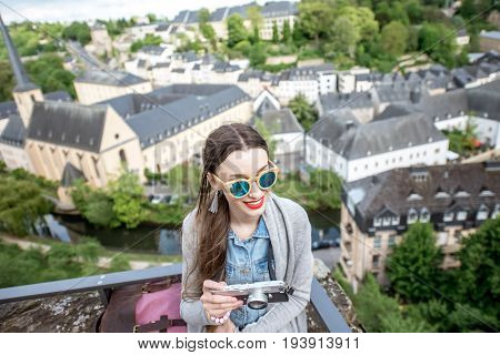 Young female traveler with photocamera enjoying beautiful cityscape view on the old town in Luxembourg city