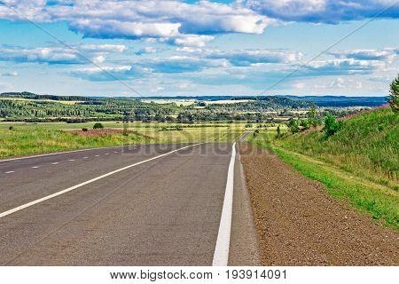 View of the winding road in the wooded hills on a summer day