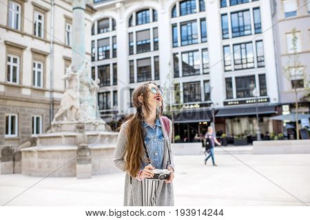 Young woman with photocamera traveling at the old town of Luxembourg city