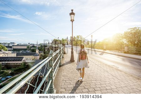 Woman walking on the bridge with great view on the old town of Luxembourg city