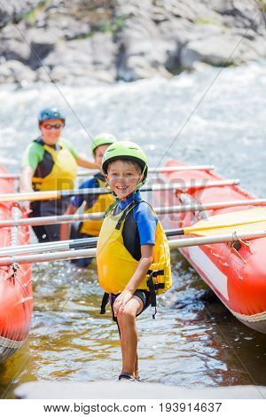 Cute boy in helmet and live vest ready for rafting on the catamaran with his family
