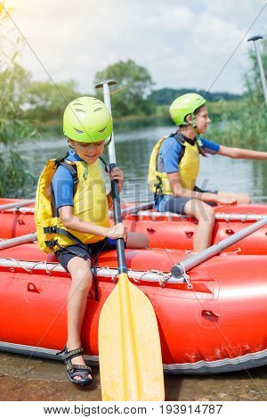 Cute boy in helmet and live vest with paddle ready for rafting on the catamaran with his sister