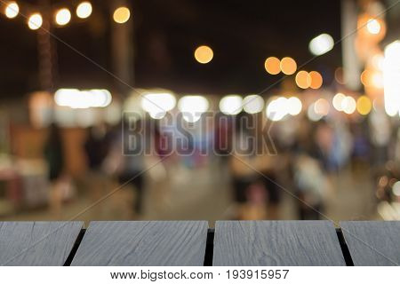 Mock up black wooden table font and blurred walking street background