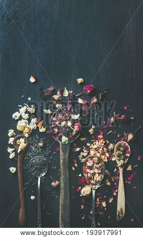 Wooden spoons with dry herbs, flower buds and tea leaves over black scorched wooden background, top view, copy space