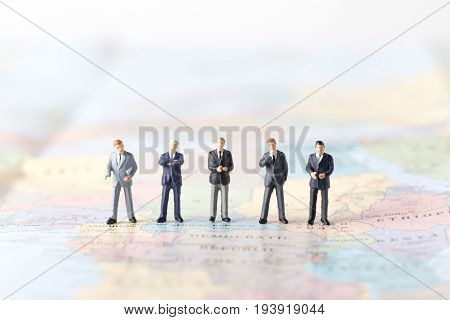 Miniature Model Group Of Investor Standing Together On World Map.