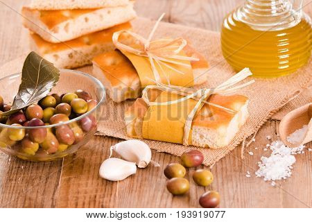 Focaccia slice bread with olives on wooden table.
