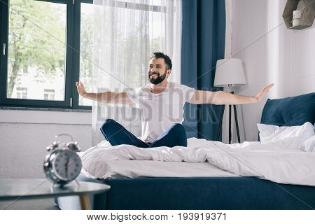 Smiling Young Man In Pajamas Stretching While Sitting On Bed At Morning