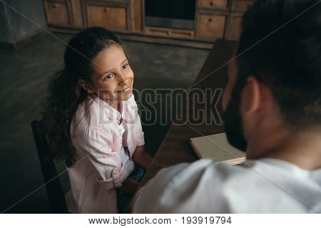 Adorable Pre-adolescent Girl Talking With Father While Sitting At Table