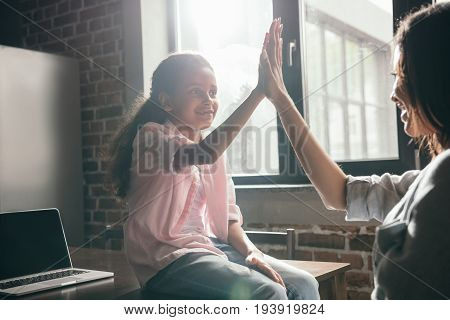 African American Daugher Giving High Five To Her Mother While Sitting On Table At Home