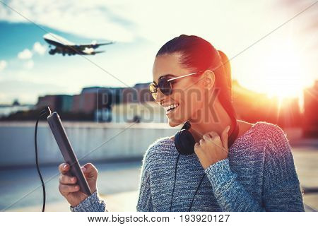 Happy young woman purchasing air ticket by tablet outdoor in sunset