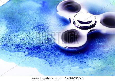 Chrome beautiful spinner on blue watercolor background with splashes. Place for your text.