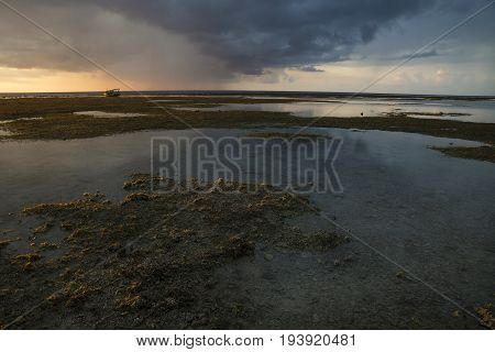 Boat at sunset and orange raincloud at Gili Air, Lombok, Indonesia