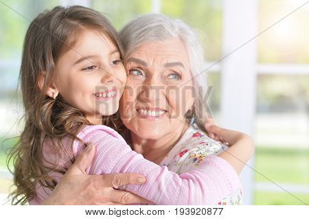 Portrait of a pretty little girl hugging her grandmother