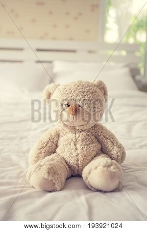 Teddy bear with depression sitting on the bed vintage color tone.