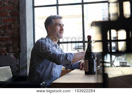 Dating in the restaurant. A handsome man offers wine