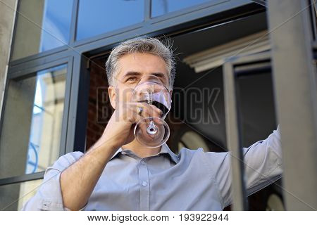 Man drinking wine. A glass of wine, a moment of relaxation on a sunny afternoon