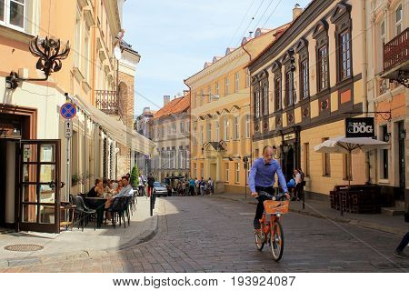 VILNIUS, LITHUANIA - JULY 18, 2015: Street in Old Town with people sitting at cafe and man riding bike in sunny day, Vilnius, Lithuania.