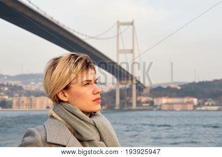 Portrait of a young woman under the Bosporus bridge