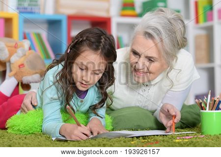 Portrait of a grandmother playing with her little daughter