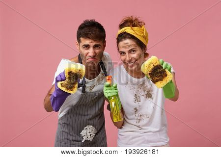Portrait Of Young Male In Apron Holding Dirty Sponge Wiping Spotes On Glass Surface Looking With Dis
