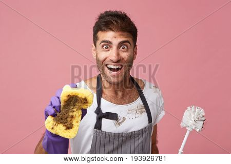 People, Housekeeping, Cleanliness Concept. Happy Man With Bristle Wearing Apron Showing Dirty Sponge