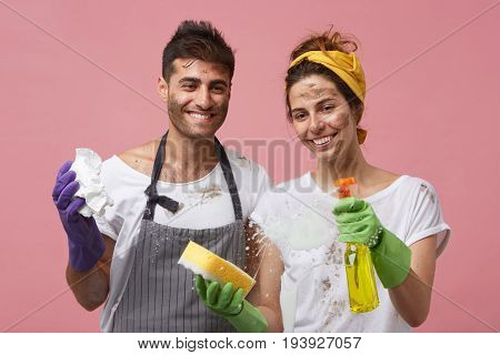 Happy Smiling Couple Washing Glass Surface Wiping Out Foam Using Sponges, Paper And Detergent Standi