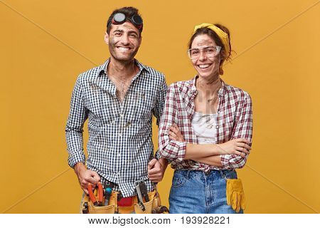 Horizontal Studio Shot Of Two Happy Confident Repairmen In Protective Wear Standing Next To Each Oth