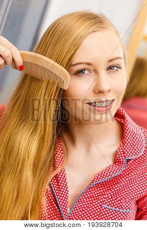Woman Combing Her Long Hair In Bathroom