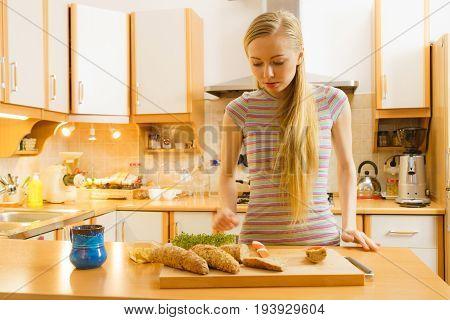Woman In Kitchen Holding Knife Making Healthy Sandwich
