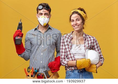 Young Male Carpenter Wearing Protective Eyewear And Mask Holding Drilling Machine Being Equipped Wit