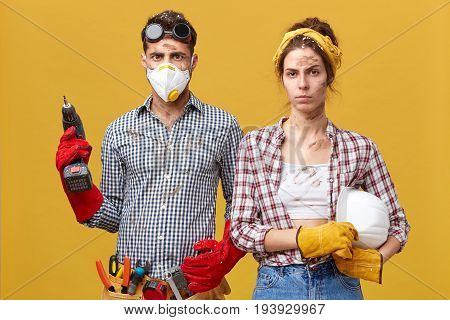 Repair, Building, Renovation And Home Concept. Serious Couple Doing Repair At Home Standing Against
