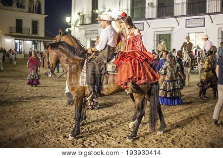 El Rocio Spain - June 4 2017: Group of pilgrims on horseback in traditional spanish dress in El Rocio during the Romeria 2017. Province of Huelva Almonte Andalusia Spain