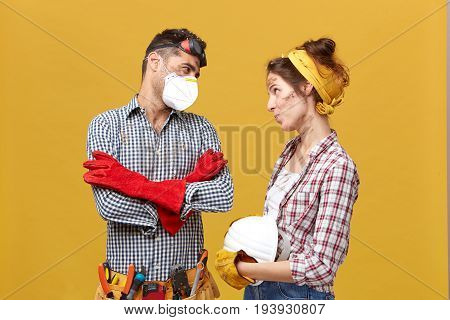 Young Repairman Standing Crossed Hands Wearing Protective Mask, Shirt And Red Gloves Looking At Her