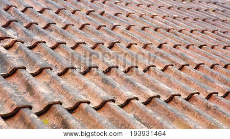 closeup of old weathered roof with red tiles