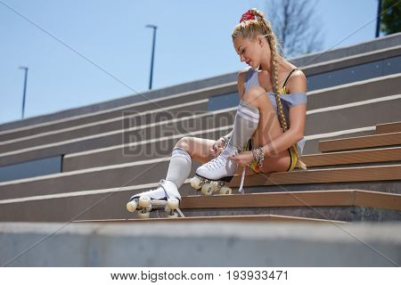 blond woman with braid over city bridge. The feet high socks and roller skates.
