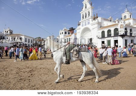 El Rocio Spain - June 2 2017: Pilgrim on horseback in traditional spanish dress in El Rocio during the Romeria 2017. Province of Huelva Almonte Andalusia Spain
