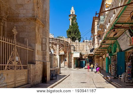 JERUSALEM, ISRAEL - JULY 04, 2016: Narrow street with souvenir shops as minaret on background in Muristan  - christian quarter, popular tourist destination, located in Old City of Jerusalem, Israel.