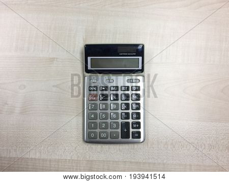 the calculator on the wood table  background