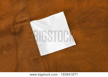 White blank clothes label on terracotta cotton as a background