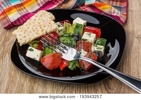 Greek Salad, Crispbread In Black Plate And Fork On Table