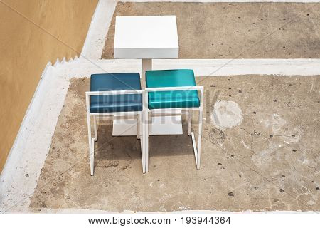 outdoor white table and two chairs near the grunge wall at coffee shop