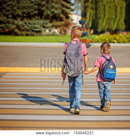 Two Boys With Backpack Walking, Holding On Warm Day On The Road.